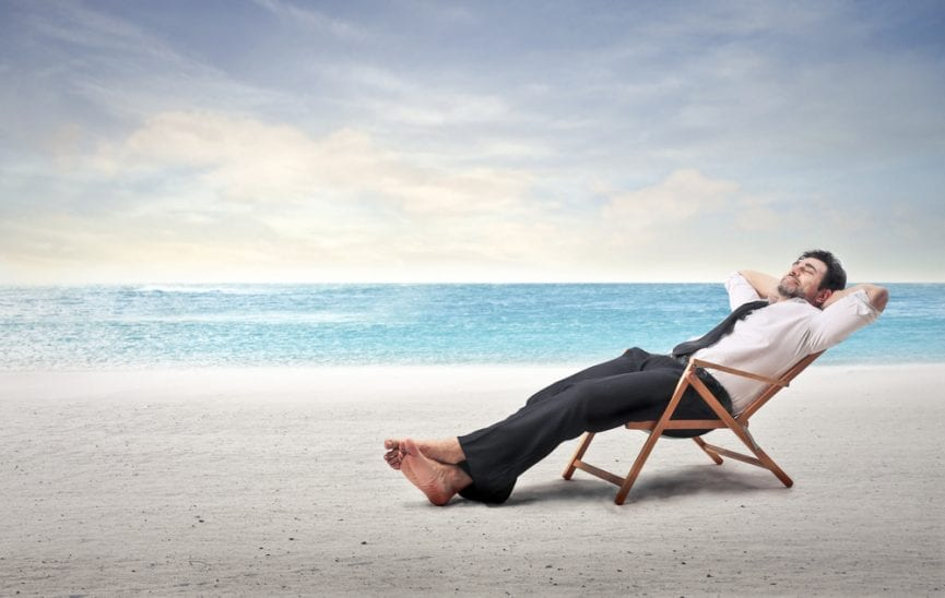 person sitting on a chair with a background of the beach