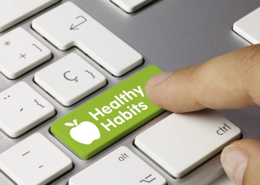 person pressing healthy habits button with a green and white background on a laptop