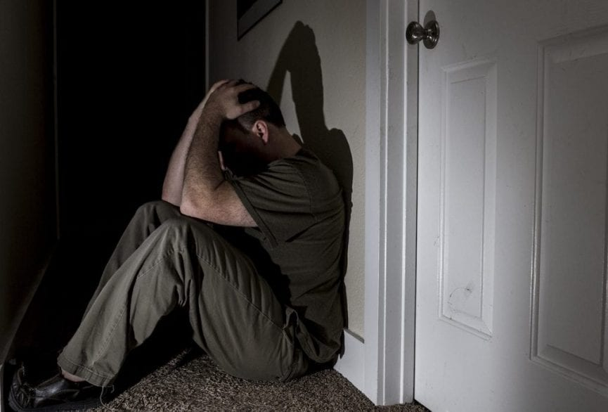 man sitting on the floor behind the white door