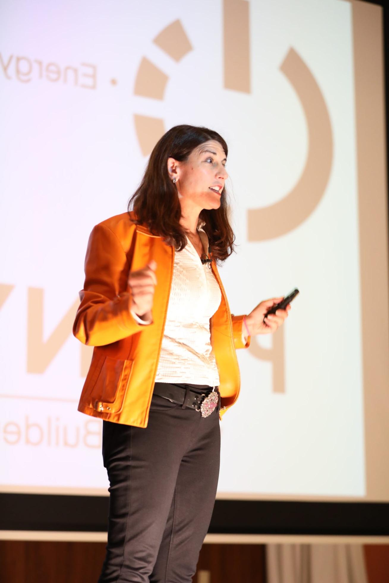 woman wearing yellow leather jacket speaking in front of a crowd