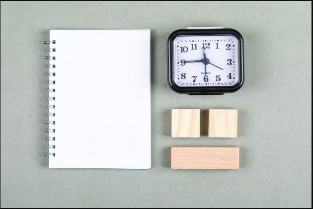 time blocking and scheduling notepad, blocks of woods and a clock