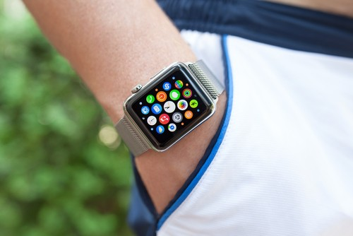 person wearing Apple Watch showing all the app icons on the screen