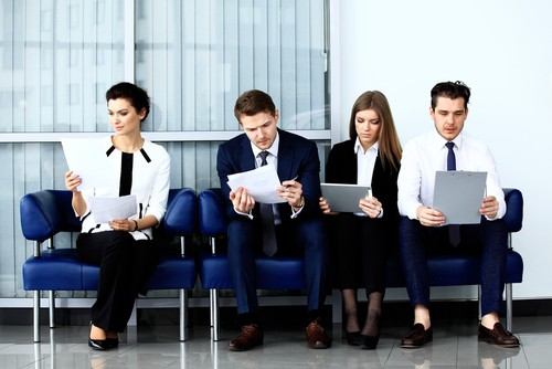 four persons wearing business attire waiting to be interviewed