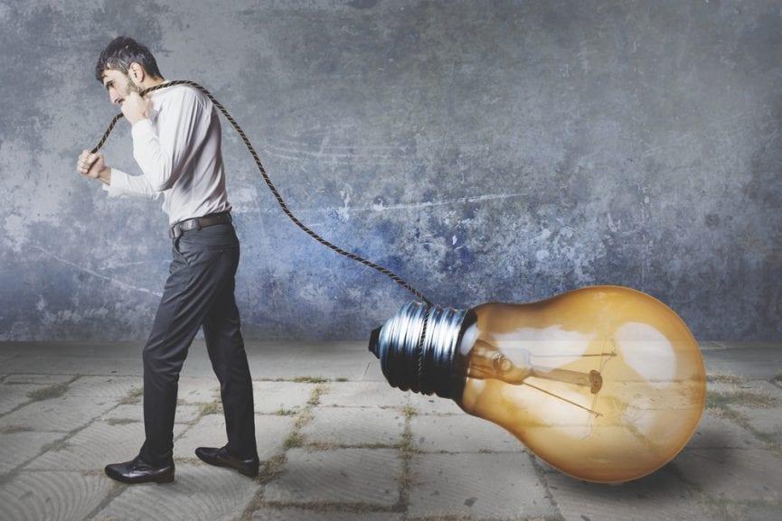 person wearing office attire pulling a big dim yellow light bulb